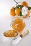 Homemade Orange jam. Bottle with homemade (real) orange jam, plate, knife and fresh oranges on back, soft focus Stock Images