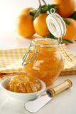 Homemade Orange jam. Bottle with homemade (real) orange jam, plate, knife and fresh oranges on back, soft focus Royalty Free Stock Images