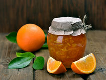 Homemade orange jam. In glass jar on wooden table Royalty Free Stock Images