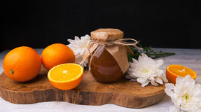 Homemade orange jam on wooden plank with flowers and oranges. Homemade orange jam in glass jar on wooden plank with flowers and oranges Royalty Free Stock Image