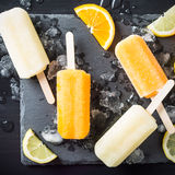 Homemade orange and lemon popsicles. With ice and citrus fruits on stone black background. Summer food concept. Top view Stock Images