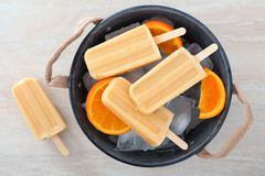 Homemade orange popsicles in a rustic ice filled tin pail. Homemade orange yogurt popsicles in a rustic ice filled tin pail with fresh fruit slices stock photo