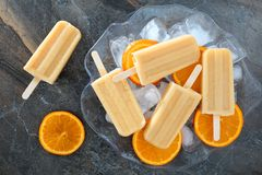 Homemade orange yogurt popsicles in an ice filled bowl Stock Photos