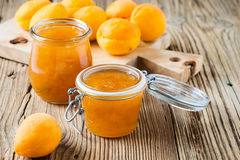 Homemade organic apricot jam in glass jar and ripe apricots Royalty Free Stock Photography
