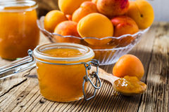 Homemade organic apricot jam in glass jar and ripe apricots Royalty Free Stock Photo