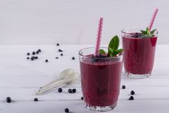Homemade organic blueberry smoothy with berries and mint leaf.