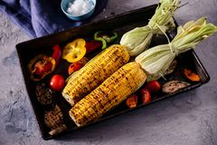 Hand uses chopsticks to pickup tasty noodles with smokes.Homemade organic grilled summer vegetables on rustic table. Corn, pepper,. Homemade organic grilled Stock Photo