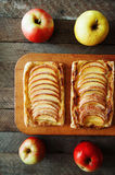Homemade organic ruddy pies with apples puff pastry, ready to eat. Delicious apple puff on a wooden table, on a rustic wood kitche Stock Image