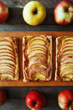 Homemade organic ruddy pies with apples puff pastry, ready to eat. Delicious apple puff on a wooden table, on a rustic wood kitche Stock Photos