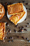 Homemade organic ruddy pies with apples puff pastry, ready to eat. Delicious apple puff on a wooden table, on a rustic wood kitche Stock Photo