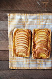 Homemade organic ruddy pies with apples puff pastry, ready to eat. Delicious apple puff on a wooden table, on a rustic wood kitche Stock Images