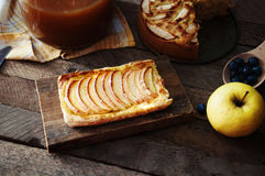 Homemade organic ruddy pies with apples puff pastry, ready to eat. Delicious apple puff on a wooden table, on a rustic wood kitche Royalty Free Stock Photography