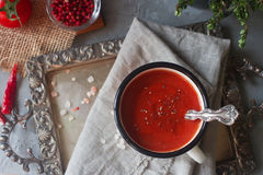 Homemade organic tomato soup in a mug with fresh herbs, garlic, red pepper and himalayan salt on vintage tray Stock Images