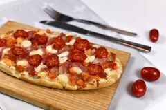 Homemade oval shaped pizzas topped with mozzarella cheese, tomato and salami sausage on wooden board