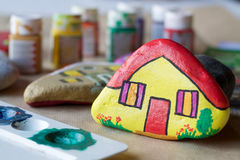 Homemade painted stones as homes. Blurred background Stock Image