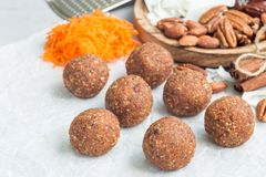 Homemade paleo energy balls with carrot, nuts, dates and coconut flakes, on parchment, horizontal, copy space Royalty Free Stock Images