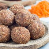 Homemade paleo energy balls with carrot, nuts, dates and coconut flakes, on wooden plate, square format. Homemade paleo energy balls with carrot, nuts, dates and Stock Photos