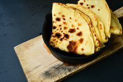 Pancakes. Homemade pancake crepe     in cast-iron pan on black background Stock Images