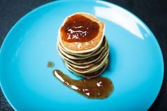 Homemade pancake with jam on a blue plate royalty free stock photos