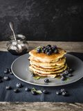Best ever pancake recipe. Homemade pancake stack decorated with blueberries and syrup; rustic wooden table with placemats and honey glass Royalty Free Stock Photos