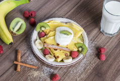 Homemade pancake with vanilla curd, raspberries, kiwi and banana pieces sprinkled with cocoa Stock Photos