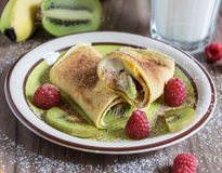 Homemade pancake with vanilla curd, raspberries, kiwi and banana pieces sprinkled with cocoa Royalty Free Stock Photos