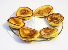 Homemade pancakes. Traditional homemade pancakes with sour cream on a glass plate, Ukrainian cuisine Royalty Free Stock Photo