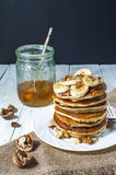 Homemade pancakes with banana slices, honey and walnuts on wooden background. Stock Image
