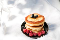 Homemade pancakes with berries: raspberries, currants on a white fabric background. healthy food. Place for text royalty free stock photos