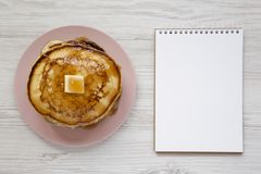 Homemade pancakes with butter and maple syrup on a pink plate, blank notepad over white wooden surface, top view. Overhead, flat. Lay, from above royalty free stock images