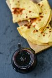 Pancakes. Homemade pancakes   in  cast- iron pan  and blueberries jam  on   black slate Royalty Free Stock Photography