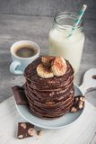 Homemade pancakes with chocolate, nuts and coffee cup. On a stone table. high-calorie breakfast royalty free stock photography