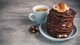 Homemade pancakes with chocolate, nuts and coffee cup. On a stone table. high-calorie breakfast stock photos