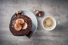 Homemade pancakes with chocolate, nuts and coffee cup. On a stone table. high-calorie breakfast. top view royalty free stock photo