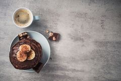Homemade pancakes with chocolate, nuts and coffee cup. On a stone table. high-calorie breakfast. top view stock photography