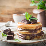Homemade pancakes with chocolate spread. Homemade pancakes with chocolate spread and mint. Healthy breakfast concept Stock Photos