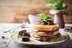 Homemade pancakes with chocolate spread. Homemade pancakes with chocolate spread and mint. Healthy breakfast concept Royalty Free Stock Images