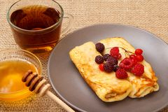 Homemade pancakes filled with cottage cheese and topped with fro. Zen raspberries and blackberries on plate, cup of tea and honey in glass bowl with wooden spoon stock photos