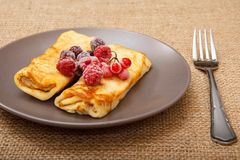 Homemade pancakes filled with cottage cheese and topped with fro. Zen raspberries and blackberries on plate and fork on sackcloth background royalty free stock photography