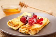 Homemade pancakes filled with cottage cheese and topped with fro. Zen raspberries and blackberries on plate and honey in glass bowl with wooden spoon on stock photography