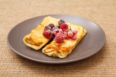 Homemade pancakes filled with cottage cheese and topped with fro. Zen raspberries and blackberries on plate and sackcloth on background royalty free stock photo