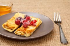 Homemade pancakes filled with cottage cheese and topped with fro. Zen raspberries and blackberries on plate, honey in glass bowl and fork on sackcloth background stock images