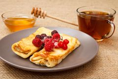 Homemade pancakes filled with cottage cheese and topped with fro. Zen raspberries and blackberries on plate, cup of tea and honey in glass bowl with wooden spoon royalty free stock images