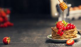 Homemade pancakes with fresh berries and honey. Breakfast set. Homemade pancakes with fresh berries and honey on rustic plate over dark wooden table Royalty Free Stock Photography