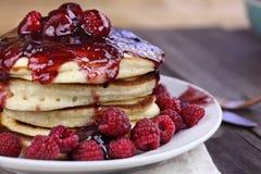 Homemade Pancakes with Fresh Rasperries and Raspberry Sauce. Delicious homemade golden pancakes with fresh raspberries and raspberry syrup. Extreme shallow depth Stock Photos