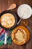 Homemade pancakes on a frying pan with sour cream. And honey on wood table Stock Images