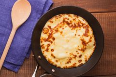 Homemade pancakes on a frying pan with spoon. Homemade pancakes on a frying pan with wooden spoon cream on wood table Royalty Free Stock Image