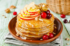 Homemade pancakes with honey, apple, cranberries and nuts Royalty Free Stock Image