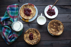 Homemade pancakes with raspberry jam on a dark wooden table. Top view with hands. Shrove Tuesday Stock Images