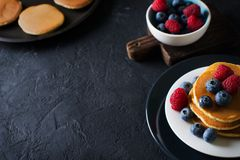 Homemade pancakes stack with berries over black texture Royalty Free Stock Photo